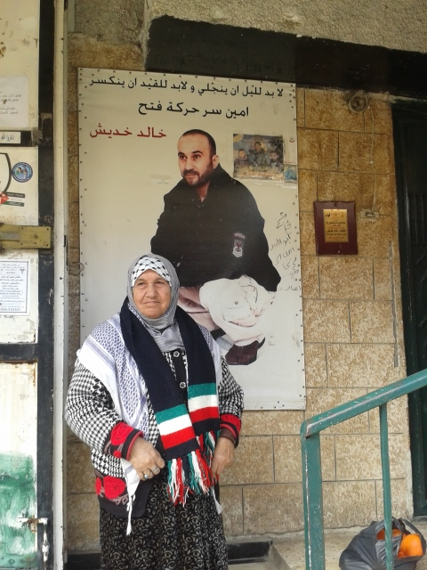 A woman inin Balata, beside the picture of her imprisoned son. Photo by Leigh Hoffman.