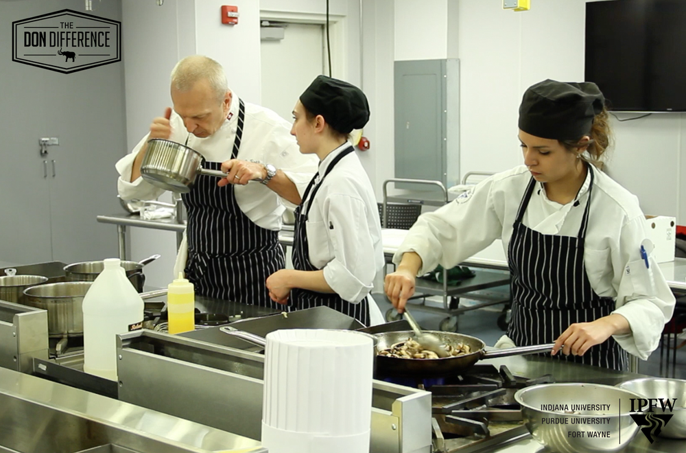 Chair of the   Department of Hospitality and Tourism Management John Niser tests the aroma of a meal prepared by his student chefs.