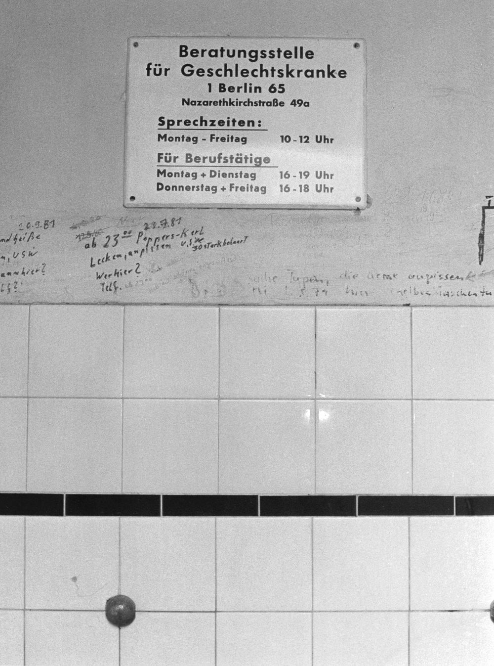 A photo of a West Berlin toilet from 1987 depicts cruising graffiti below a sign directing patrons to a sexual health clinic