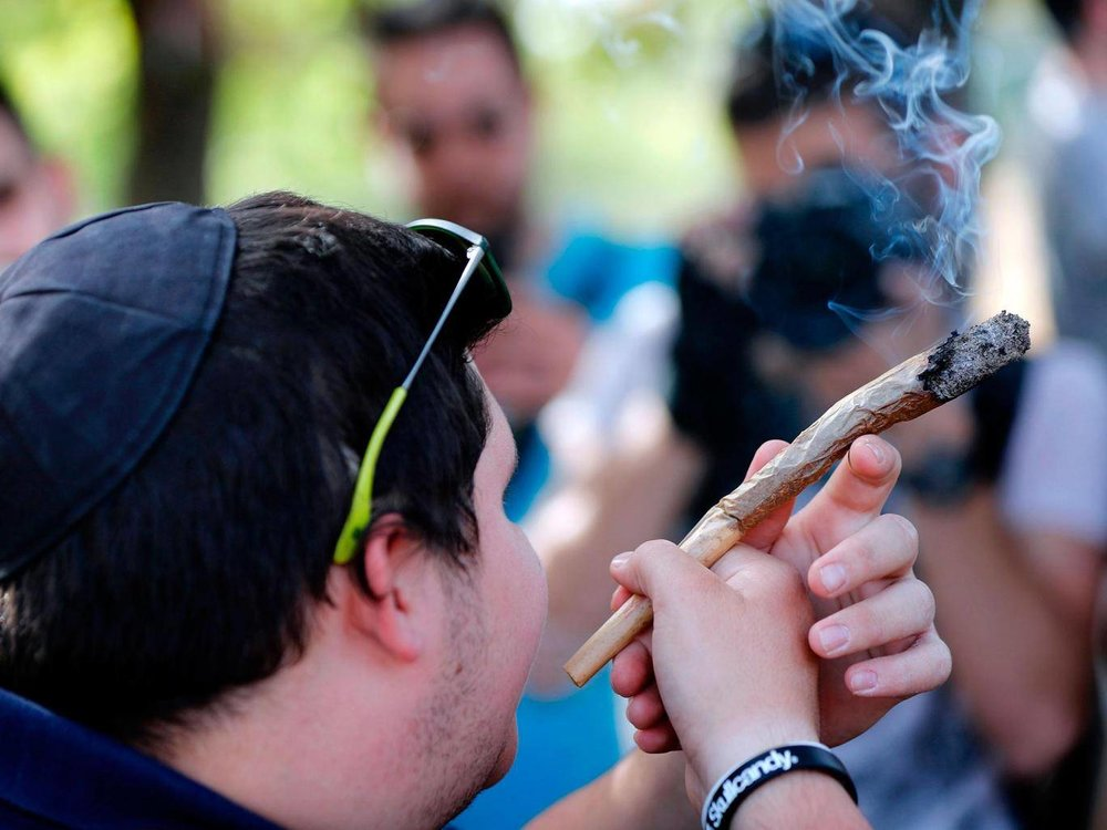 An Israeli man smokes a giant marijuana joint during a rally to celebrate '420' in the Rose garden, just across from the Knesset THOMAS COEX/AFP/Getty Images