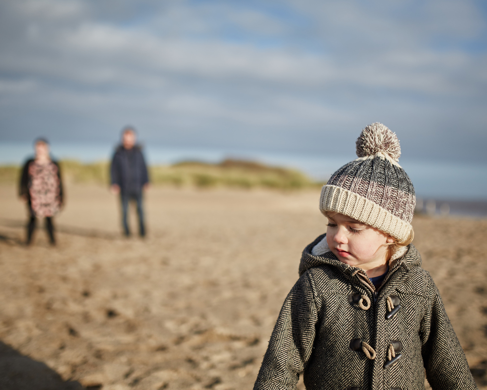 A boy and his parents on the beach