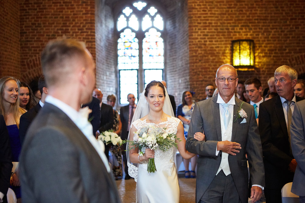 A father walks a bride down the aisle in Lincolnshire on their wedding day.