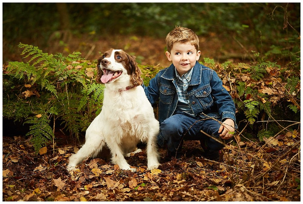 A woodland family portrait of a boy and his dog in Lincolnshire