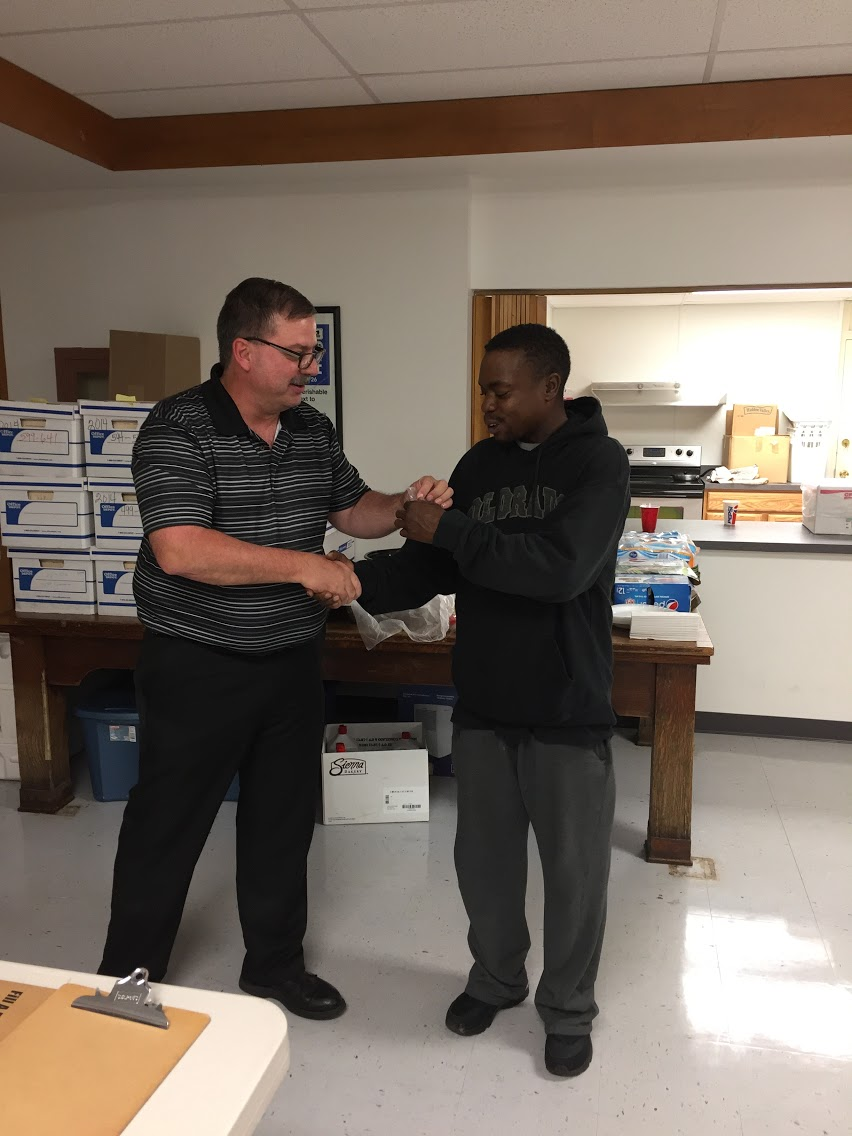 Jamal Grinston receiving his membership pin from President Hornyak