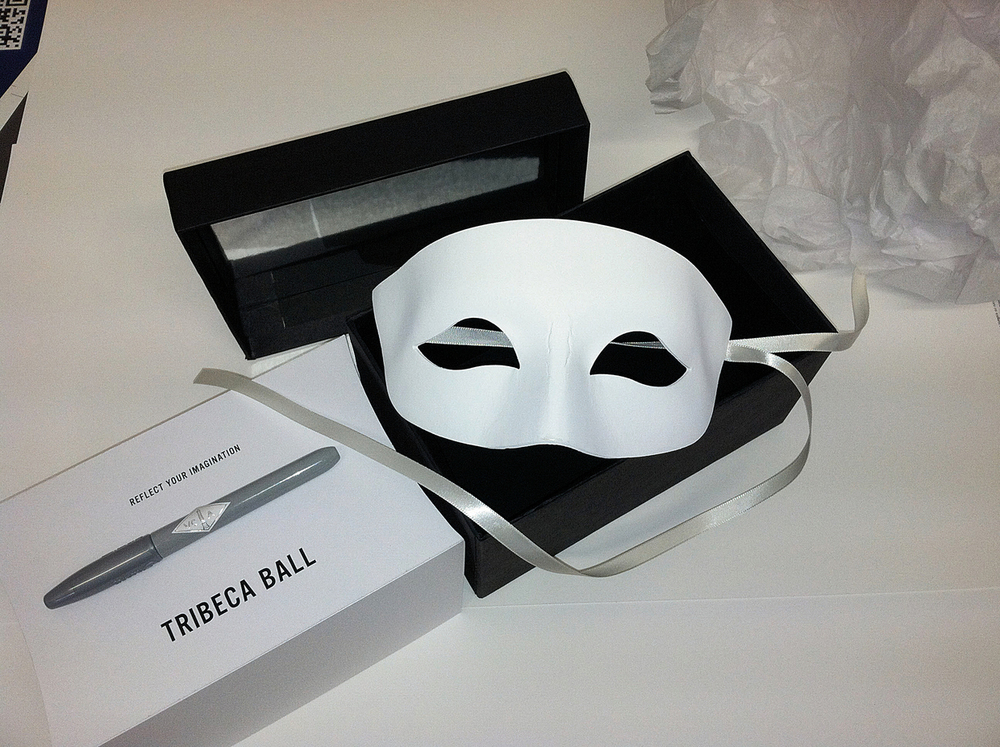 The dinner guests each receive a tray-served presentation box containing a white, handmade mask that they are encouraged to personalize with their own vision for the evening.