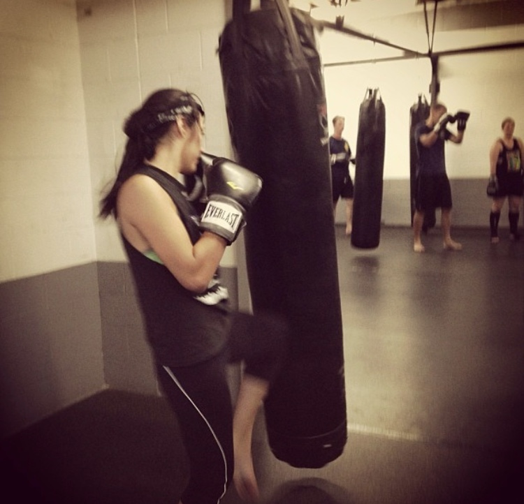 Janelle Herrera throwing a lead knee strike during a KM Kickboxing class.