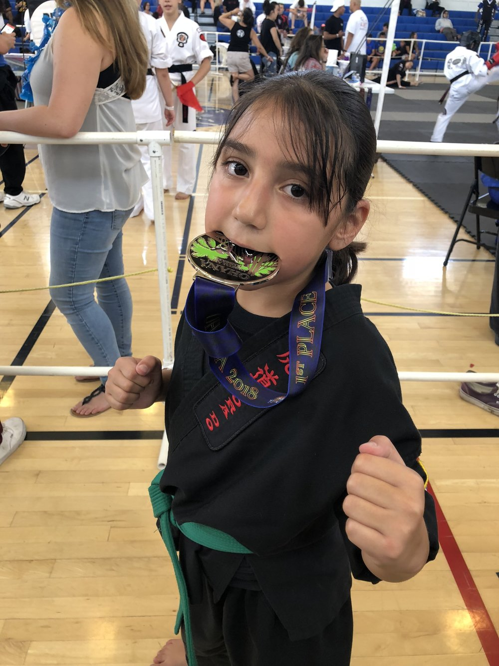 "Natalie Cruz  (8) ""tastes gold"" for the first time after winning 1st Place in her division for Sparring at what was her first tournament. Cruz competed against older and higher ranked students. Cruz is excited for the next competition."