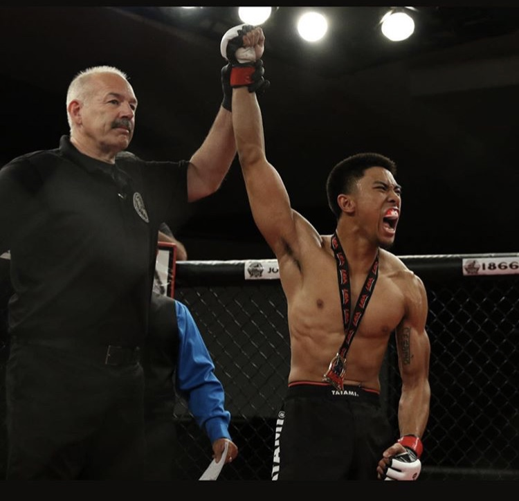 Denzel Rosaroso  has his hand raised after a submission victory in the first round