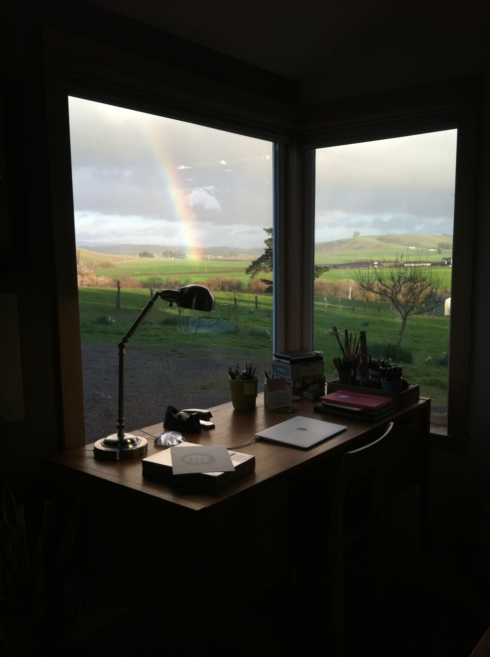 My desk in the corner of the living room + nature's art of a rainbow outside