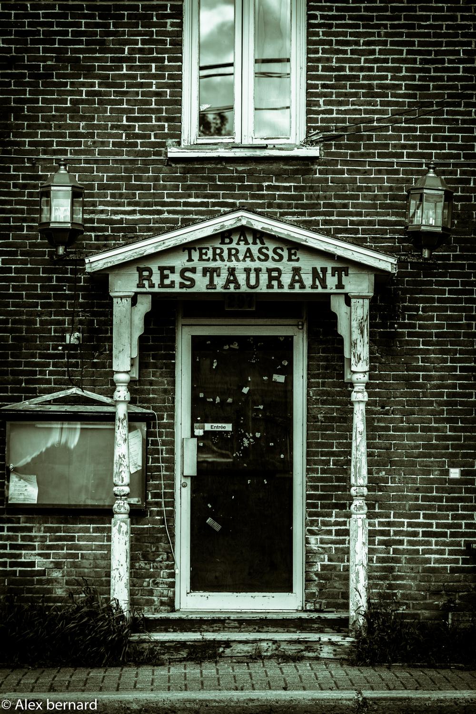 Je ne connais pas les raisons qui ont mené à la fermeture de ce restaurant du vieux #Saint-Jean-sur-Richelieu, mais ce n'a surement pas été la clarté de son nom. On se demande bien si les trois éléments sont placés en ordre d'importance. Est-ce que c'était le genre d'endroit où j'allais pour prendre un verre sur la terrasse et je restais tellement longtemps sur la terrasse que je finissais par me commander un petit quelque chose à manger ? Une chose est certaine, le propriétaire aimait que les choses soient claires en nous indiquant sur la porte qu'il s'agissait bel et bien de l'entrée.