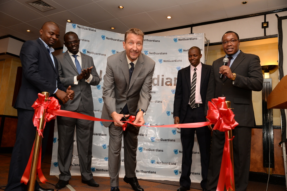 The Deputy to the Swiss Ambassador to the Republic of Kenya His Excellency Mirko Giulietti as he cuts the ribbon to mark the official opening of NetGuardians Africa offices.