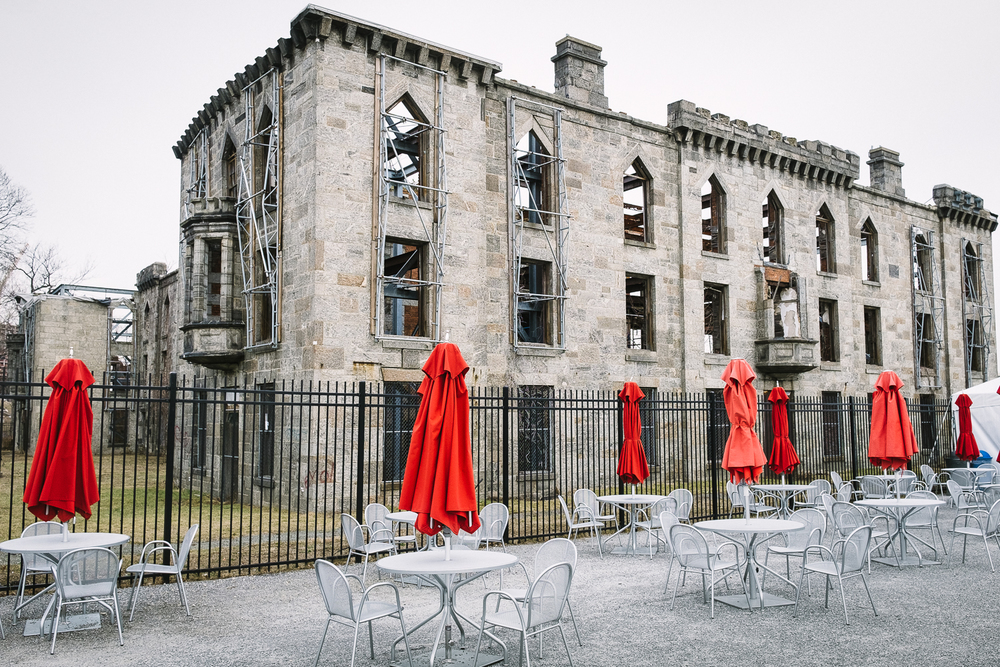 An odd combination: the ruins of a 19-century smallpox hospital and the red umbrellas from the food concession area at Southpoint Park on Roosevelt Island, New York.