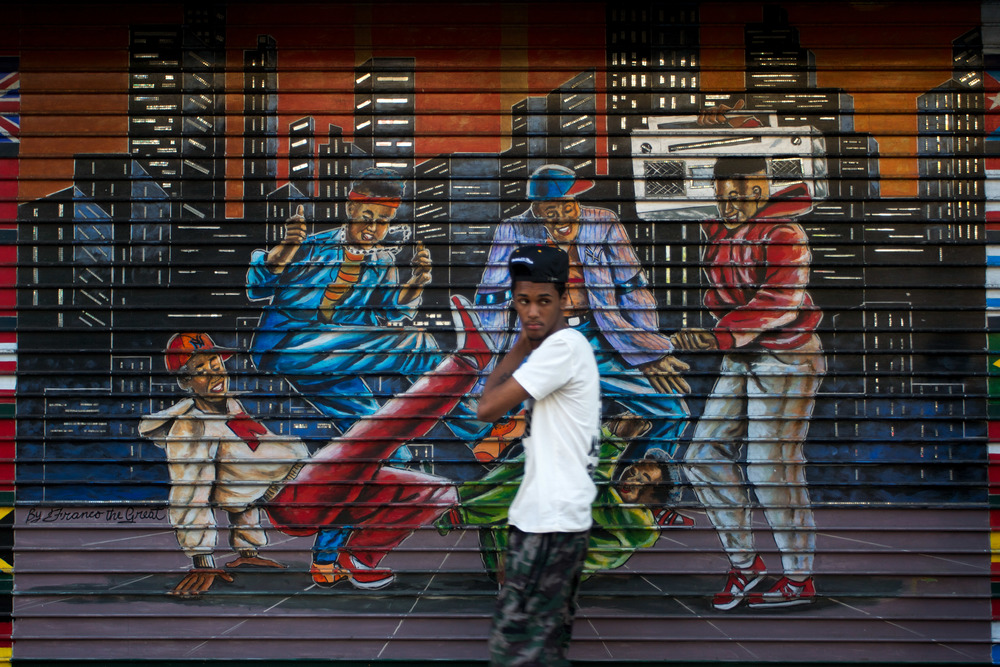 A Harlem resident passes a local mural celebrating local culture.