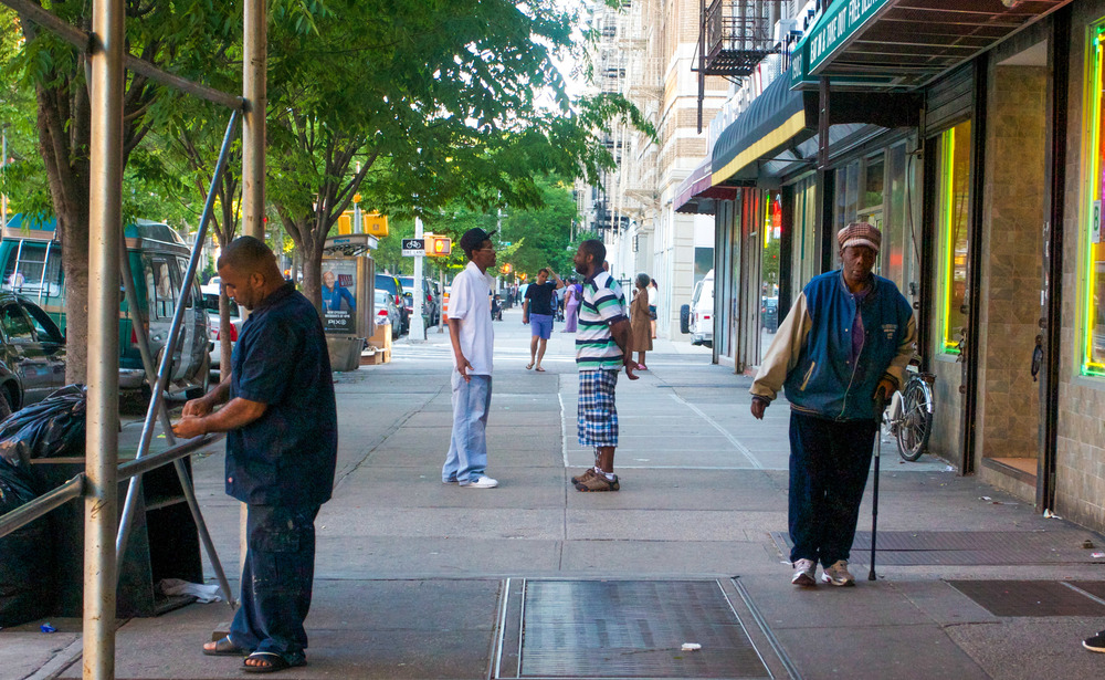 Residents talk, amid passerby's on a street corner in Harlem.