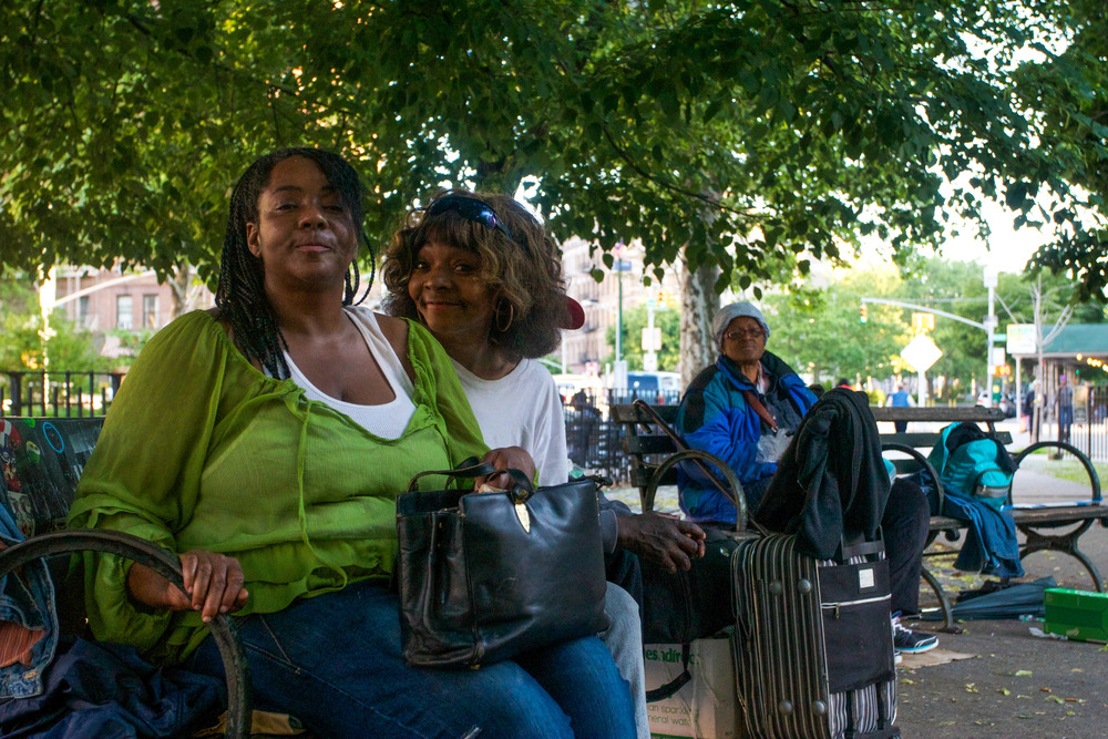 "Residents sit with who they call ""homeless harlemites"" on benches at a small park."