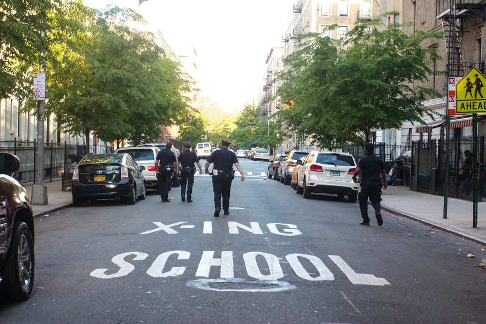 New York police officers are stationed to patrol the road in a school zone.