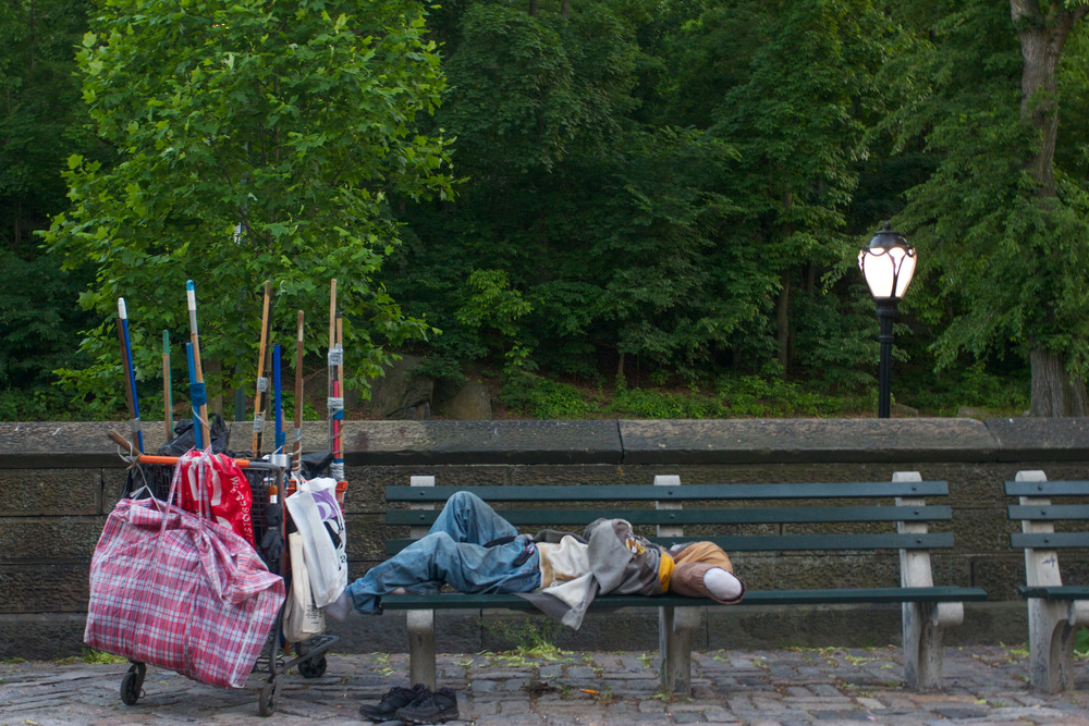 A homeless resident sleeps on a park bench near Central Park.
