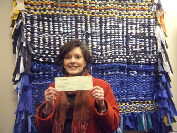 Lee Aylward, program associate for education and community outreach for the Delta Center for Culture and Learning, holds a check from the Deer Creek Foundation.
