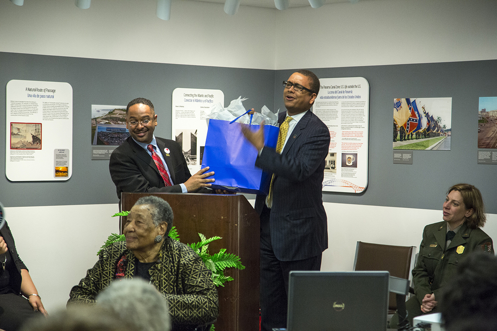 Dr. Rolando Herts gives a token of appreciation to Mossi Tull on behalf of The Delta Center and the Mississippi Delta National Heritage Area. Tull sponsored travel for Delta Jewel Annyce P. Campbell and her family, as well as Reena Evers, to participate in the Delta Jewels program at Smithsonian Anacostia. (Photo courtesy of Smithsonian Institution)