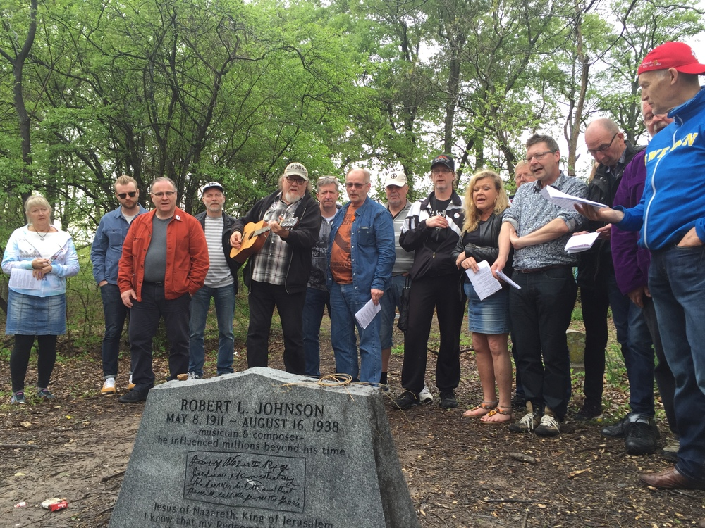 Klaus Engström leads the group in a Robert Johnson song as they visit one of the three gravesites for the Blues legend.