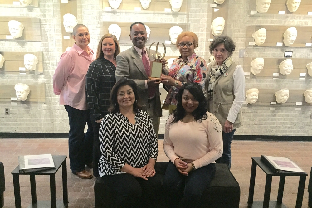 Dr. Rolando Herts receives the Georgene Clark Diversity Champion Award from Arlene Sanders, Diversity Committee chair (center) on behalf of The Delta Center, along with staff members (left to right) Patricia Webster, Heather Miller, Lee Aylward and student employees Lydia Haley and Moira Fair. Student employees not pictured include Stephanie Green and Erica Spiller.