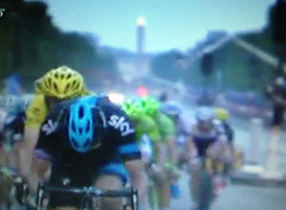 Le Tour de France with riders and the obelisk gleaming in the background