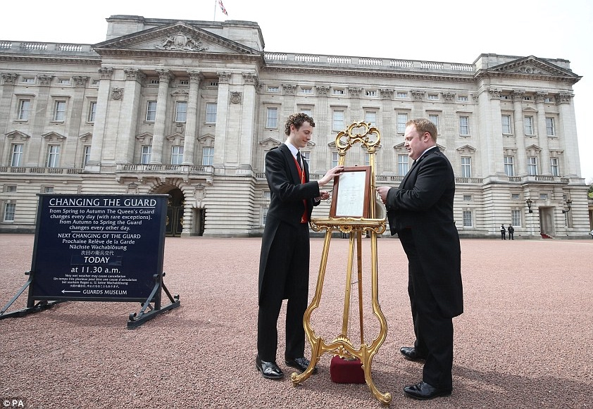 Two footman place the traditional birth notice signed by Kate's medical team on a golden easel outside Buckingham Palace.