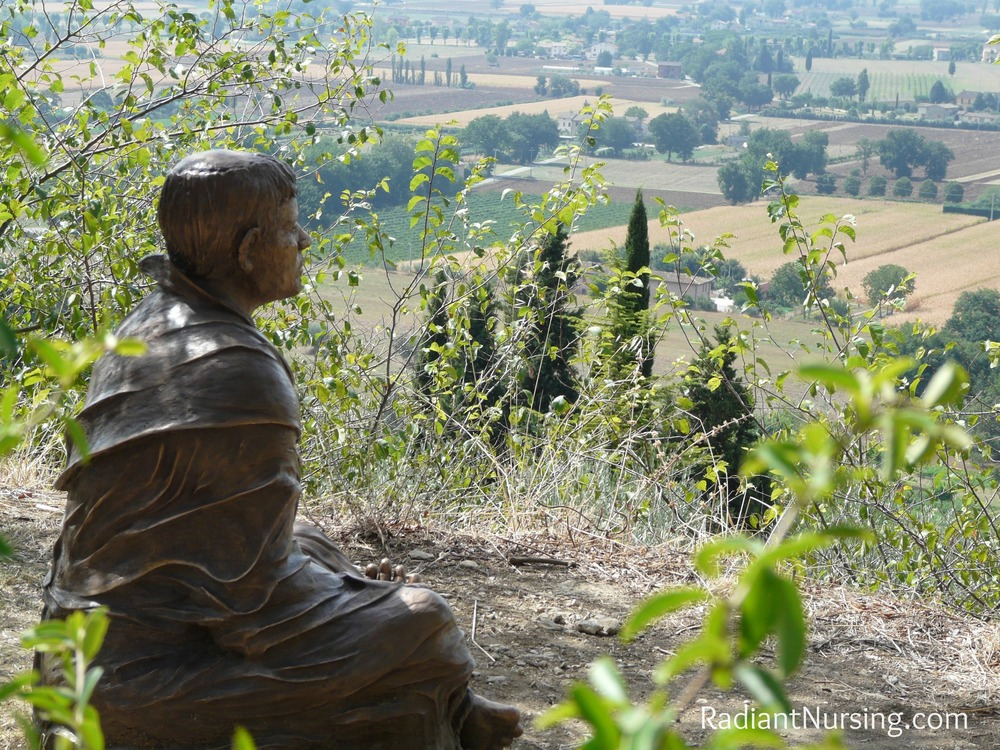 Statue of St. Francis in prayer and meditation overlooking the valley of Assisi.