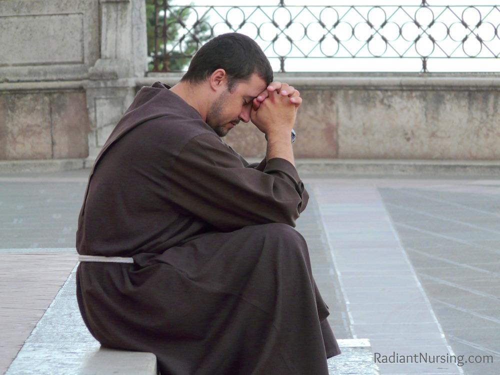 A monk in prayer sitting on the steps outside in Assisi.
