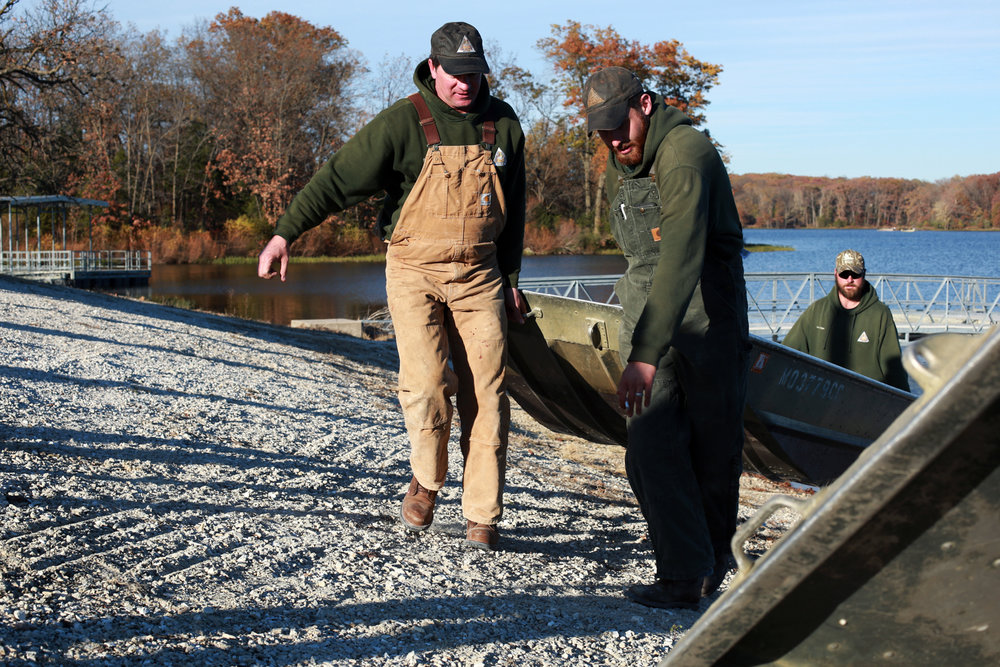 After a brief outing on Little Dixie Lake, James, alongside William Ferguson and Alex Geiger, return a boat back to shore. During a mid-day slow period of chronic wasting disease testing, James unlocked a boat, which had been chained down for winter, and allowed two MDC employees to row out and collect fishing bobbers that had become stuck out on the lake.