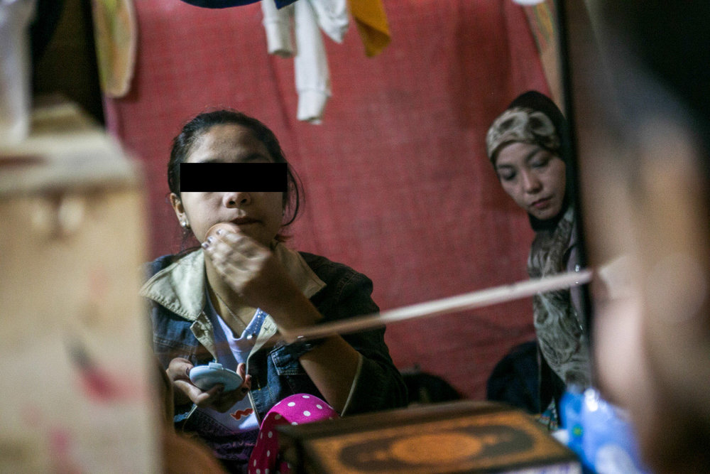 Fatima applies makeup before leaving for school. Despite the tough conditions in the evacuation center, she and her family try to live a normal life.