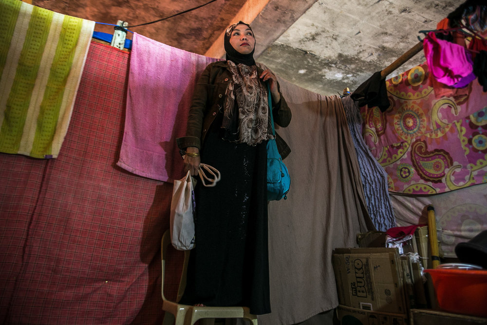 Noraidah stands on a chair to see if the alleged bully is in the corridor or standing by the entrance. Noraidah and Fatima's cubicles are located near the front entrance of the building where the boy's mother would hangout with her friends.