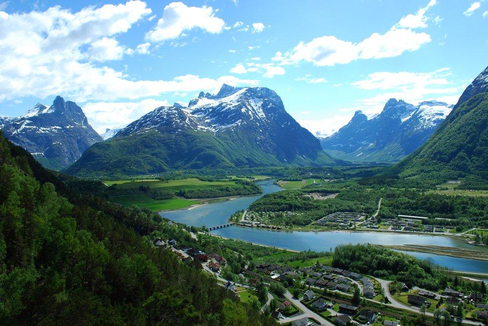 Her ser man Romsdalshorn til venstre i bildet, Adelsfjellet i midten og Kongen, Dronningen og Bispen til høyre. Campingen ligger ved siden av broen på bildet.                  Foto by: Leif J Olestad