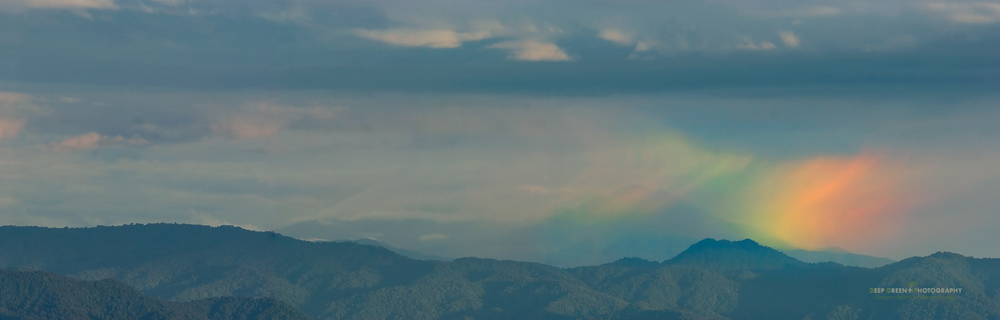 a rainbow forms over the Tilaran Mountain Range in Costa Rica
