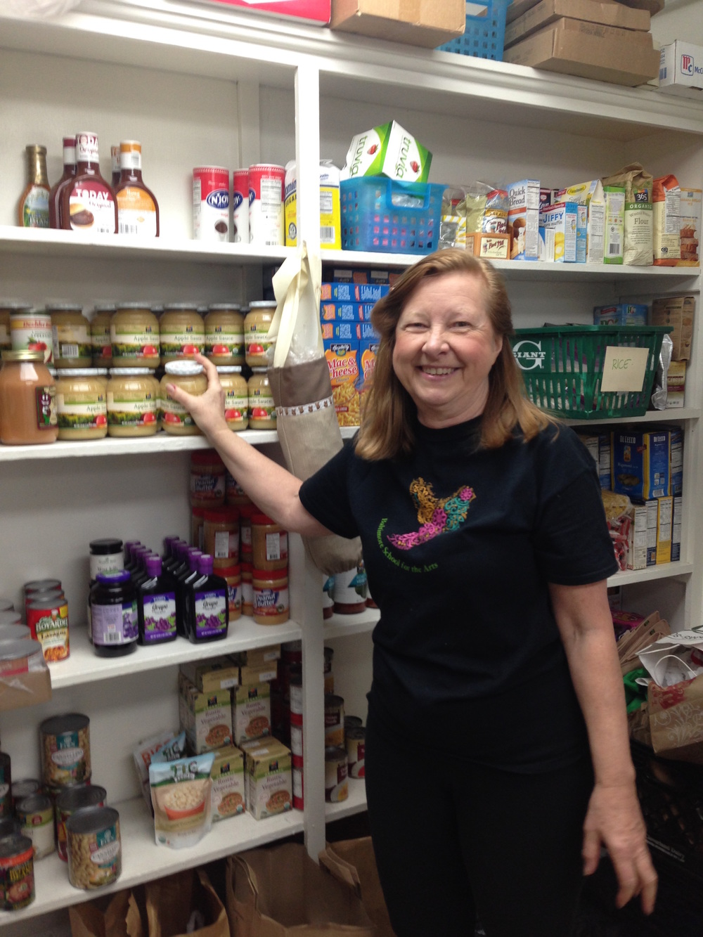 Coleen, one of our regular volunteers, prepares the food pantry for members by stacking the shelves.