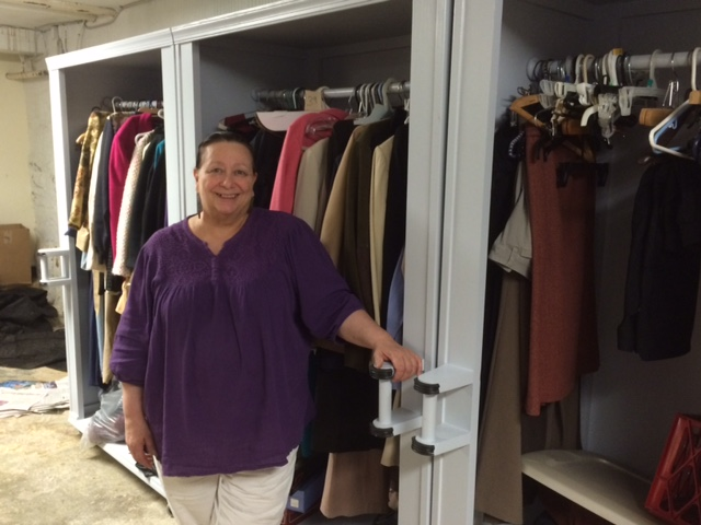 "Sharon Krieger, Program Director at Samaritan Community, shows off the new custom-built closets in the newly expanded Clothing ""Shop""."