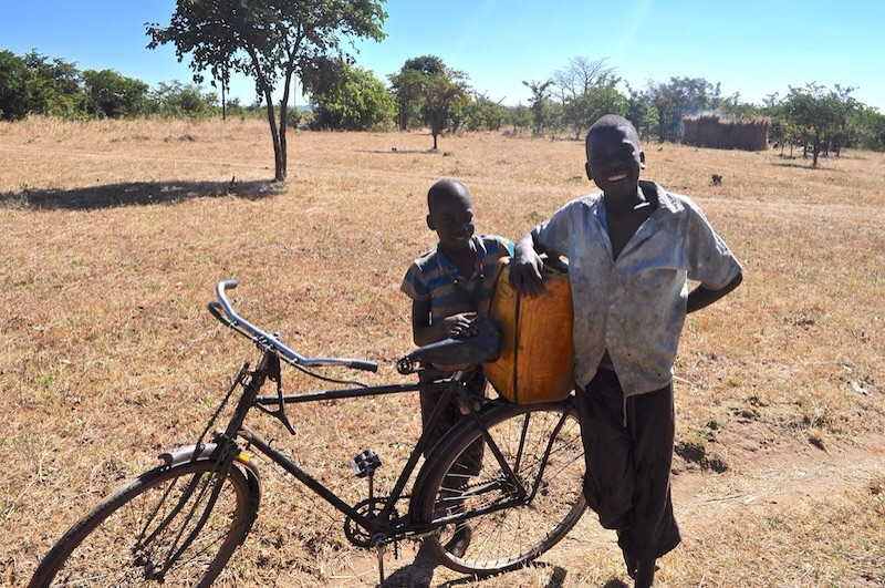 Two young boys carry water on their bike from Cohombe