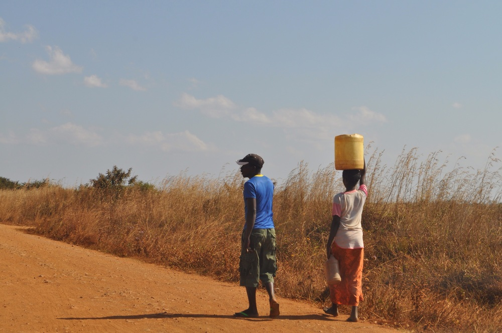A common sight on the road... Woman carrying multiple jugs of water while the man carries nothing...
