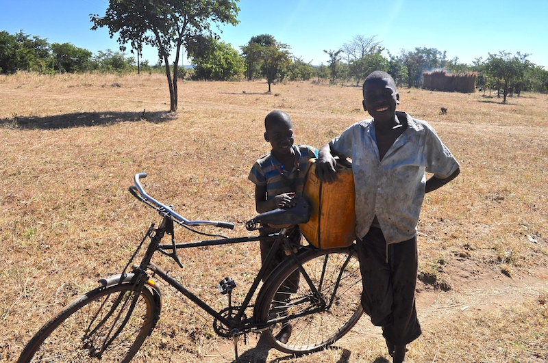Two boys gather water in Cohombe Village