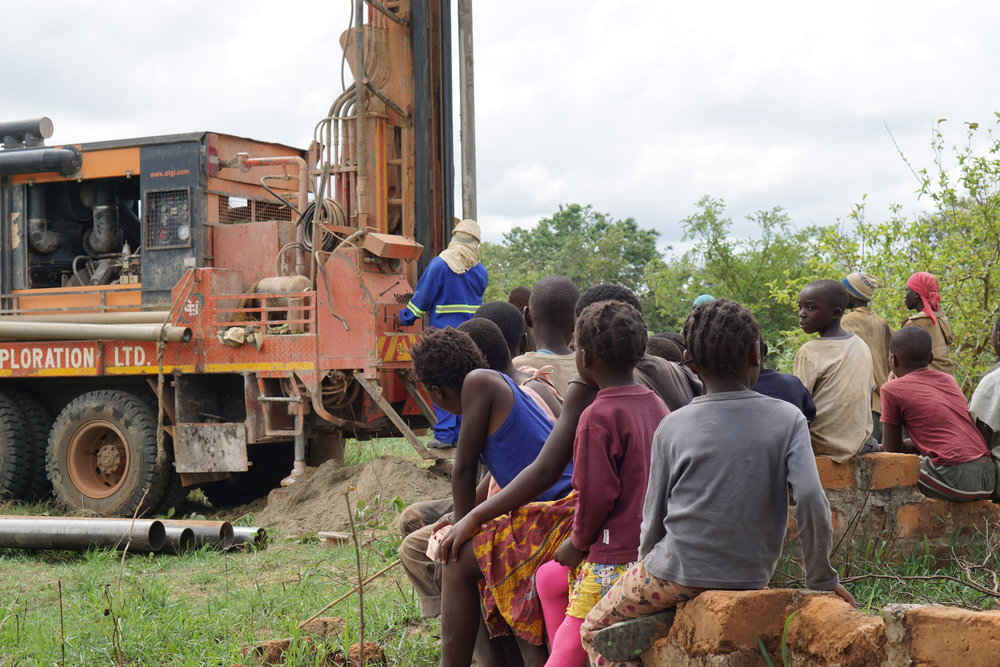 Children spectators as a drill rig brings clean water to Chinkila Village