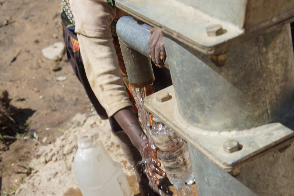 Young girl gets water to drink from borehole well