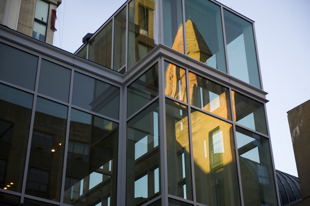 CAS reflects in the glass of the new The Sumner M. Redstone building in the evening light September 3, 2014.  Photo by Cydney Scott for Boston University Photography