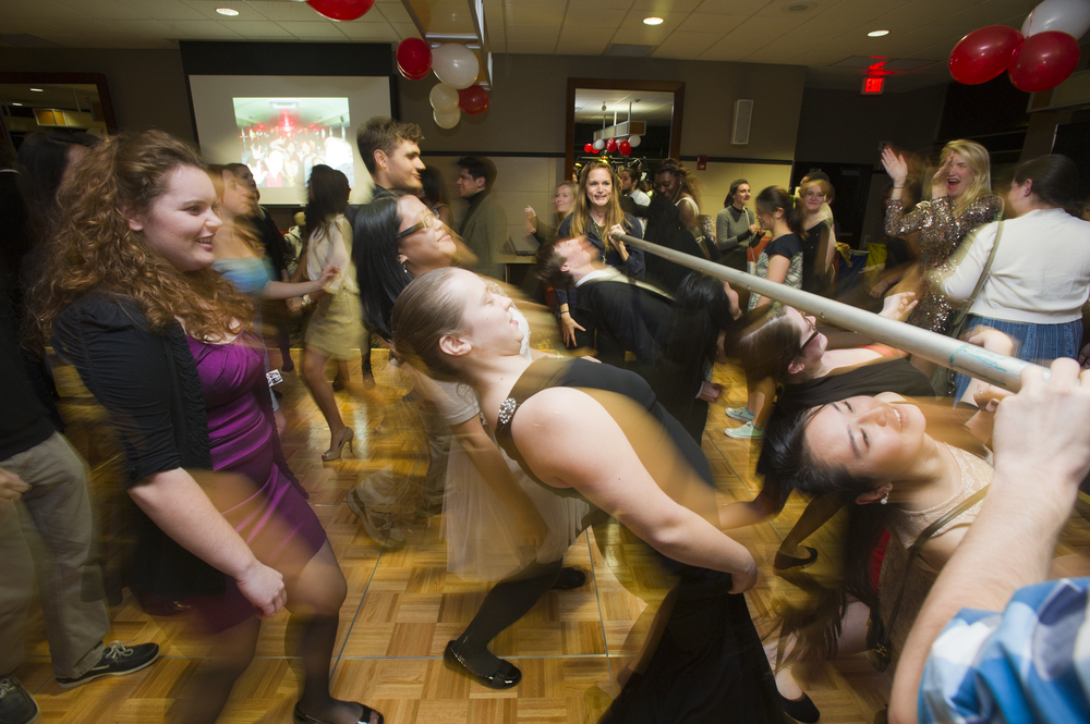 Revelers take on a limbo pole during the Deaf Studies Club ASL Ball November 14, 2014 in the GSU backcourt.  Photo by Cydney Scott for Boston University Photography