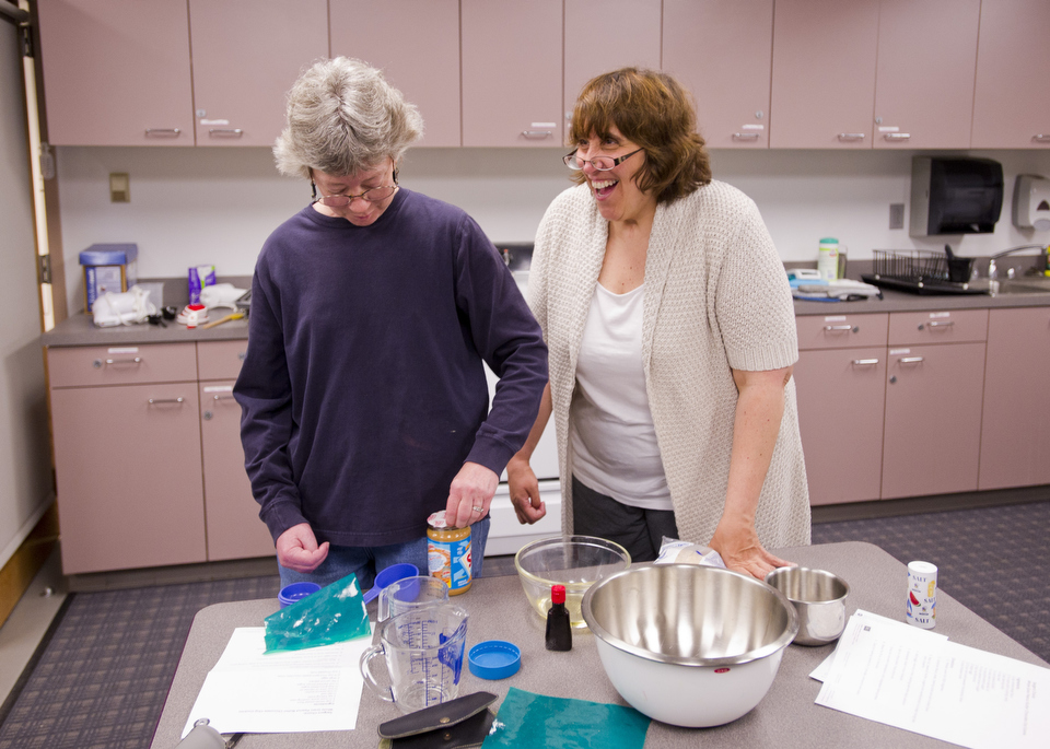 Pat Dennis of Concord, left, and Mary Borrelli of Lynn manage to retain their sense of humor even when OT sessions get frustrating. This is for a story about a summer program for Aphasia patients at Aphasia Resource Center at SAR.  Photo by Cydney Scott  for Boston University Photography
