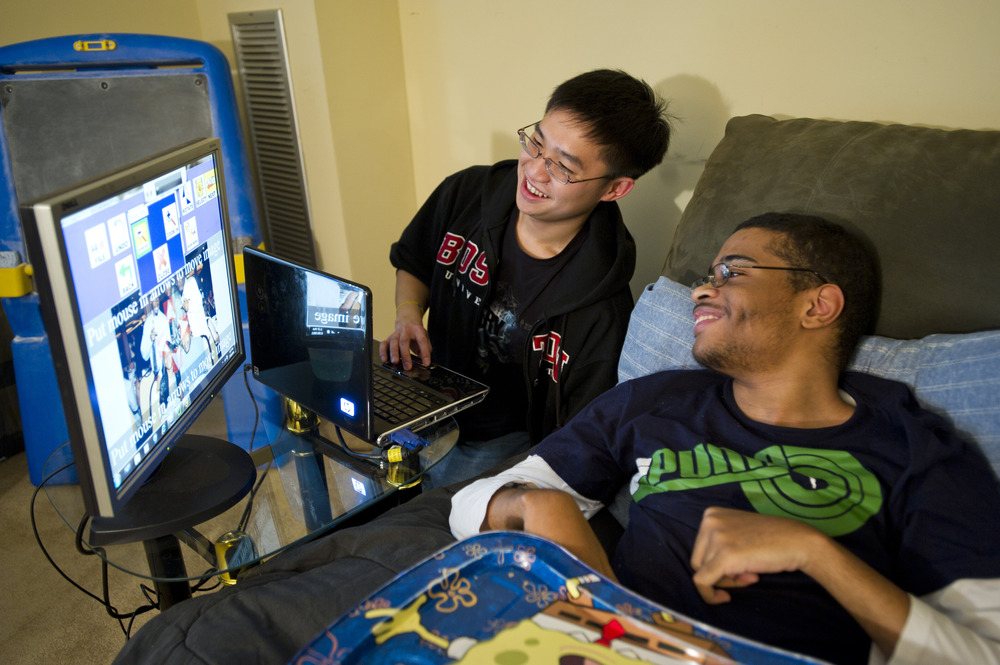 Chris Kwan, at left, is a computer science research student in UROP who is developing a software that allows users will mobility impairments to edit photos. Here, Kwan shows his software to Corey Petitt of Boston and has him try out they editing system in Petitt's home.  Photo by Cydney Scott  for Boston University Photography