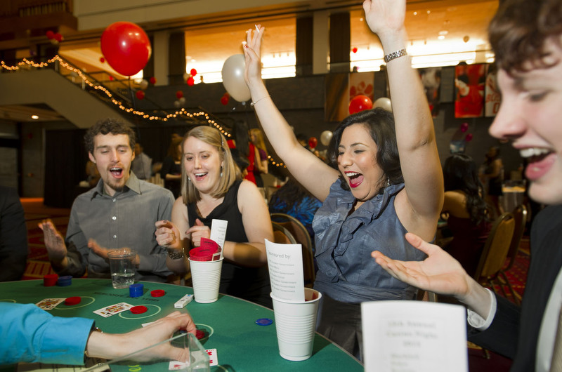 Aaron Fisher-Katz (ENG,'14), left,  Sarah Wiegard (SAR,'13), second from left, and Kevin Flynn (CAS,'14), right, look on while Ana Sofia Camacho (ENG,'13), celebrates the hand she was dealt during the 15th Annual Casino Night at the GSU February 3, 2012. All proceeds from the Mad Men themed event went to iChase The Cure.  Photo by Cydney Scott for Boston University Photography