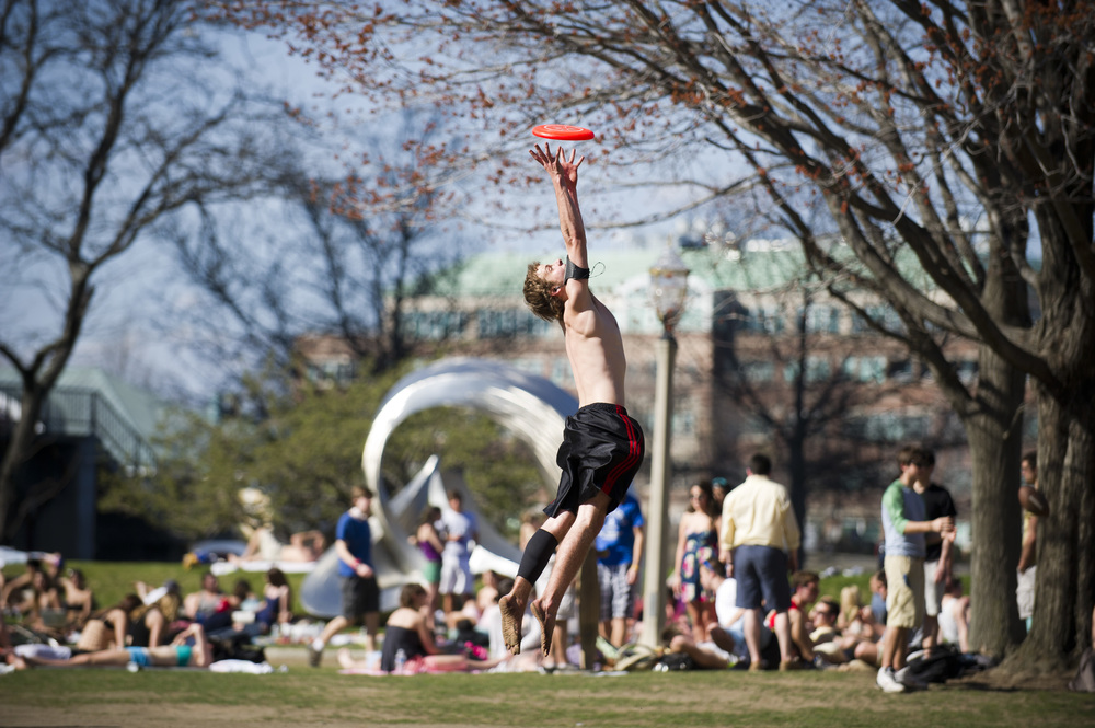 Andy Beckenbach (ENG'13) enjoys some frisbee with friends on BU Beach March 22, 2012. The crowd at BU Beach was massive thanks to the bright sun and hot temperatures.  Photo by Cydney Scott for Boston University Photography
