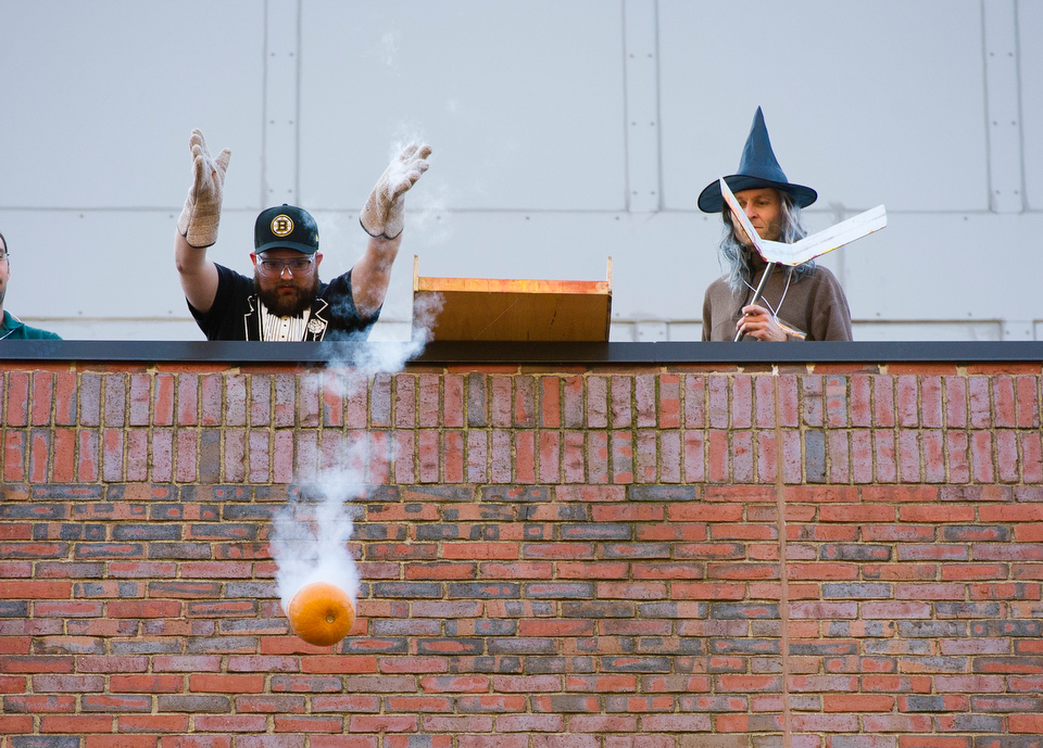 Professor Martin Schmaltz, at right, looks on while John Ogren (ENG grad) lets go of a pumpkin that's been frozen in liquid nitrogen off the roof of the Metcalf Science Center during the Annual Pumpkin Drop October 26, 2012.   Photo by Cydney Scott for Boston University