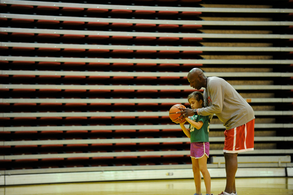 BU Mens Basketball Coach Joe Jones works with his daughter Alicia Gomez, 7, during the Joe Jones Basketball Clinic at Case Gym July 8, 2013. The four day clinic, which runs through Sunday shooting, focuses on ball handling and individual offensive and defensive skills.  Photo by Cydney Scott for Boston University Photography
