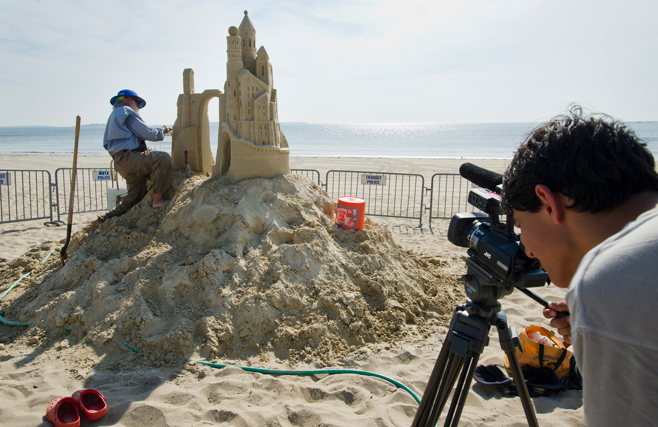 COM's Academy of Media Production (AMP) student  Dyan Fam, 15, of Winchester collects footage of The Amazin' Walter McDonald of Texas as he creates his sand sculpture. COM Assistant Professor Chris Cavalieri brought the students to the Revere Beach Sand Sculpture Festival to shoot on-site video.   Photo by Cydney Scott for Boston University Photography